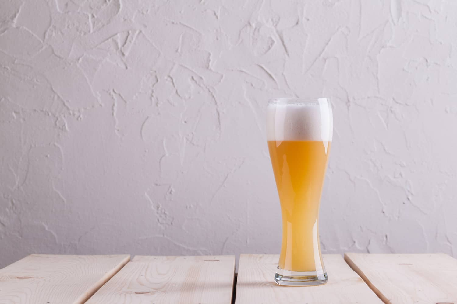 Full glass of hefeweizen wheat beer on a light wood table