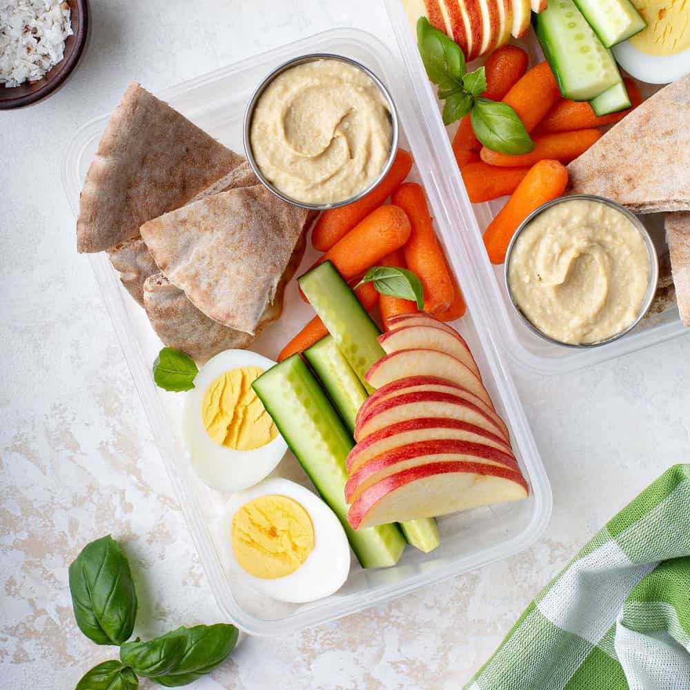 Healthy snack boxes to go with hummus and pita, eggs and vegetables