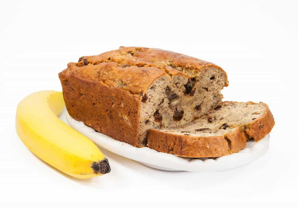 Homemade banana bread with raisins on a white dish with a banana against a white background