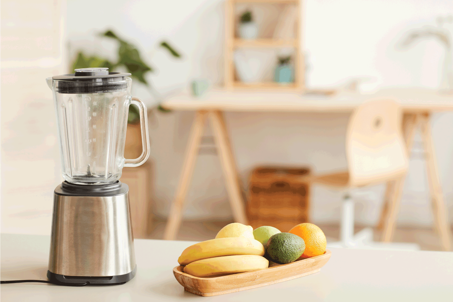 Image of fresh fruits prepared for cocktail with blender standing on the table in the kitchen