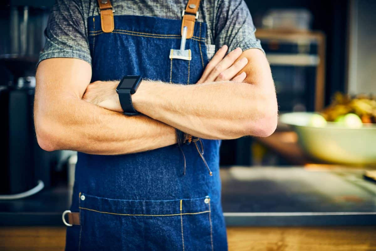 Midsection of confident barista wearing smart watch. Young man is standing with arms crossed. Waiter is wearing apron in coffee shop, 11 Types Of Aprons And Their Uses