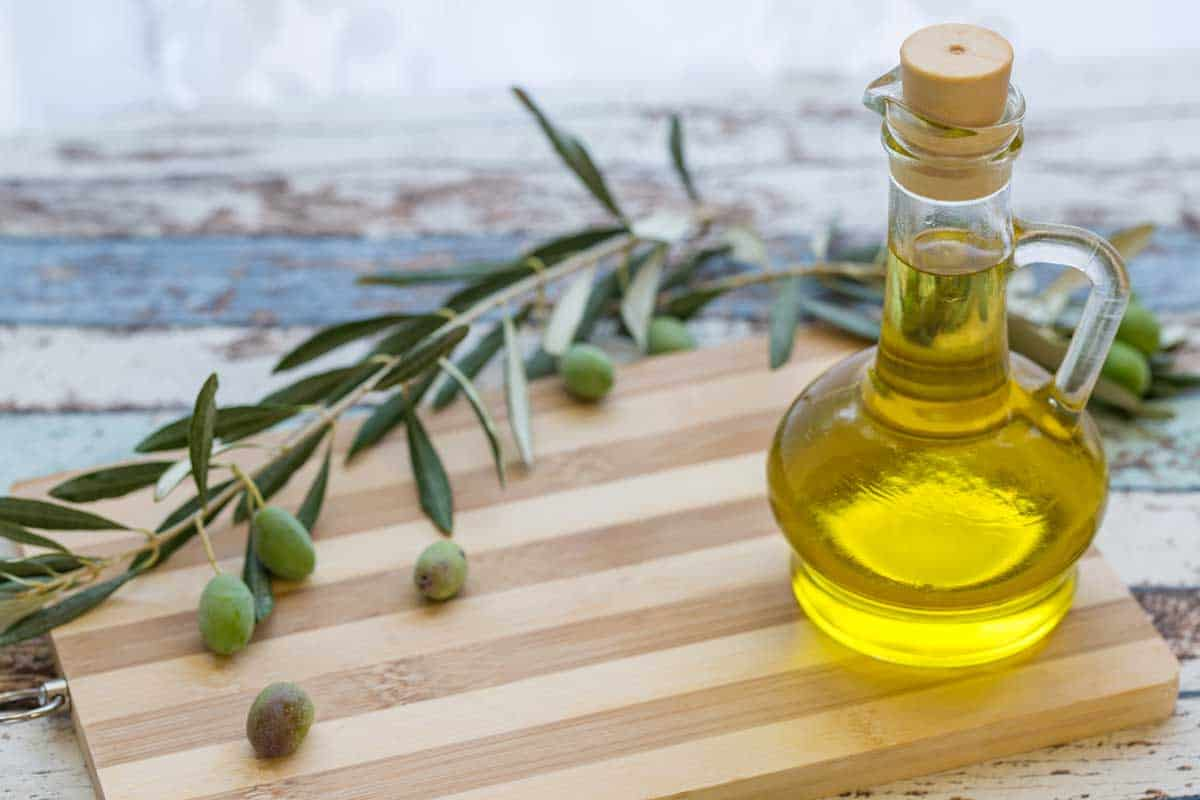 Olive oil in glass and olive on cutting board, What Oil Is Best For Butcher Block Or A Cutting Board?