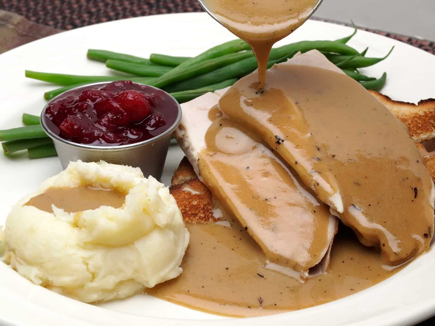 Open Face turkey sandwich with green beans, cranberry sauce and mashed potatoes with gravy pouring over potatoes and meat.