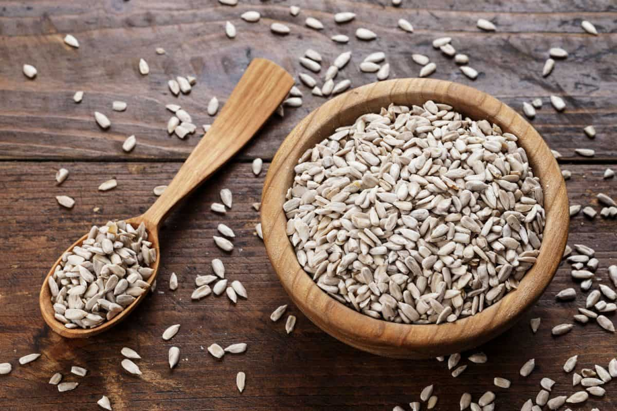 Peeled sunflower seeds on a wooden background in a plate