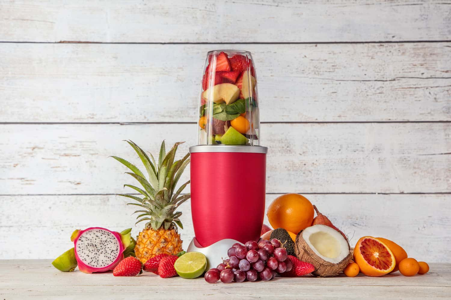 Smoothie maker mixer with pieces of fruit ingredients, placed in wooden interior