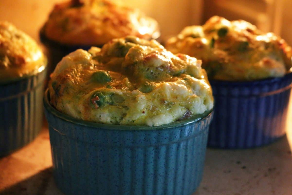 Stock photo showing inside of hot oven with egg and spinach breakfast muffin served in blue ramekin dishes being baked