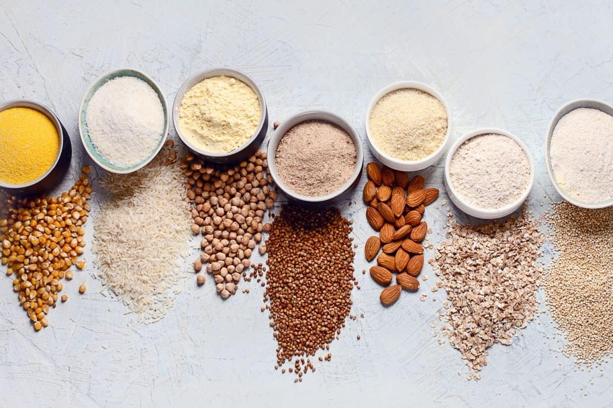 Various gluten free flour - chickpeas, rice, buckwheat, quinoa, almond, corn, oatmeal on grey background