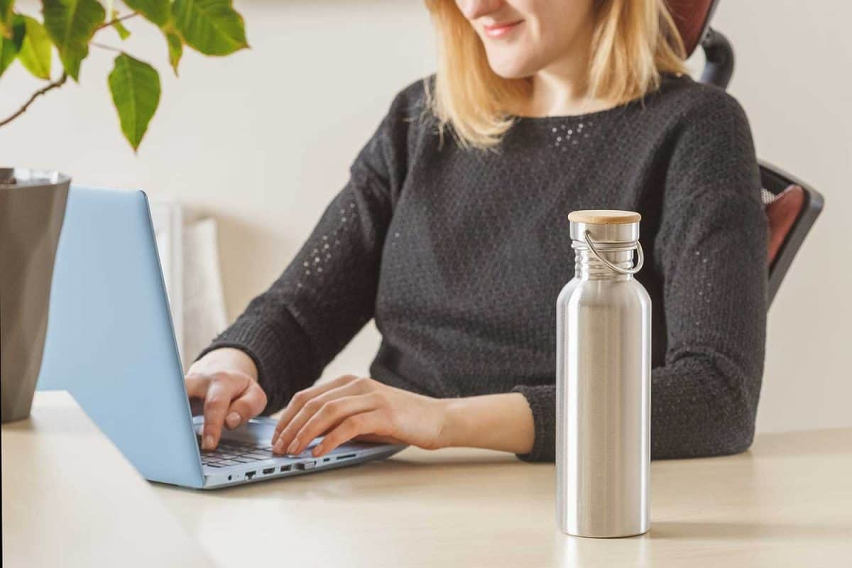 Woman keeps her steel water bottle on the table to hydrate herself during working day at office