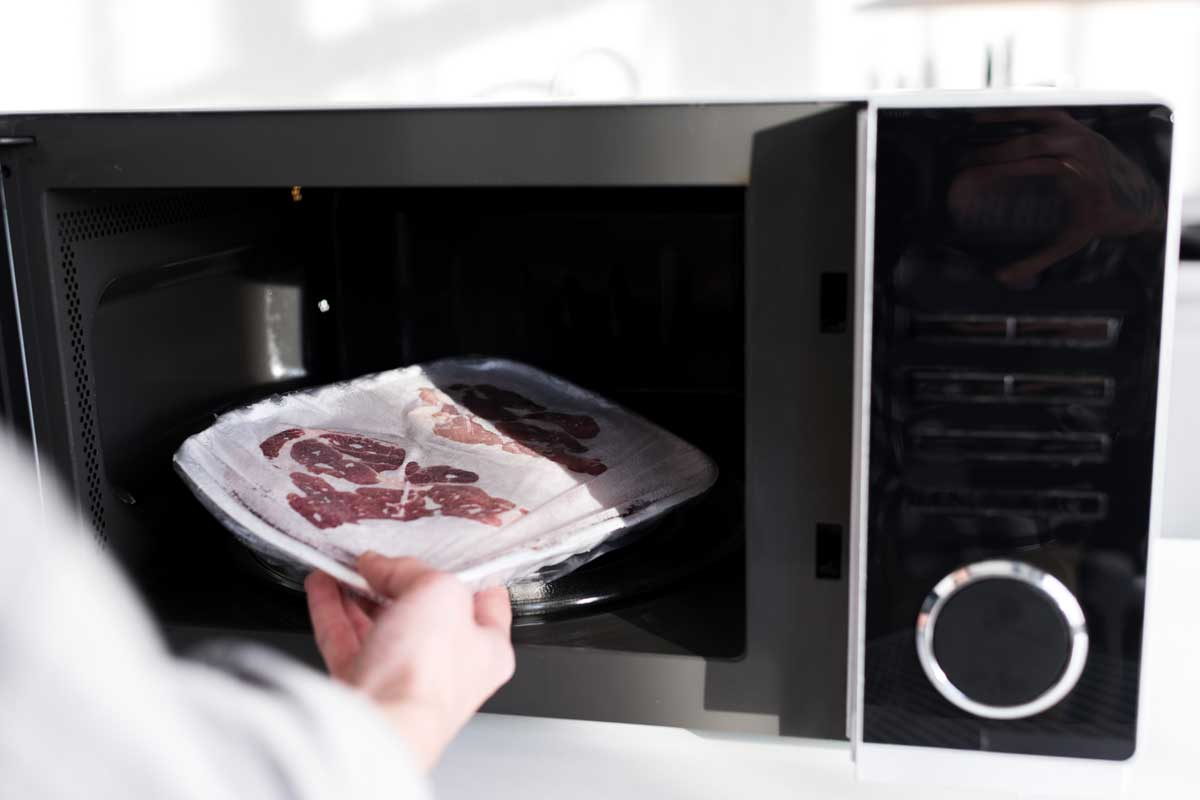 Woman putting meat into microwave in kitchen, Does Microwaving Meat Make It Tough?