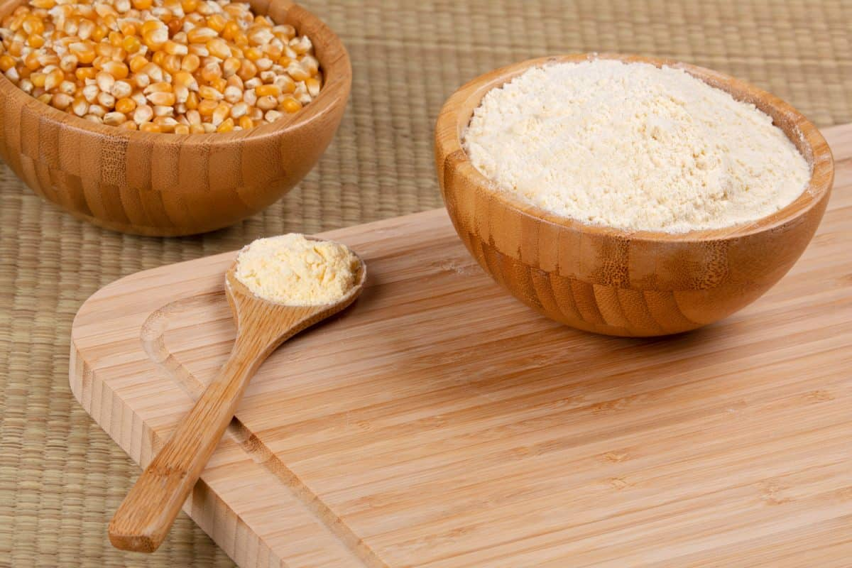 Wooden bowl of cornmeal or cornflower and wooden spoon full of cornmeal on a wooden background