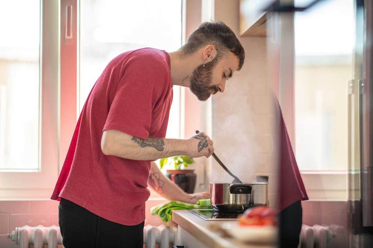 Young man bending over cooking pan on the stove and stirring food with spatula