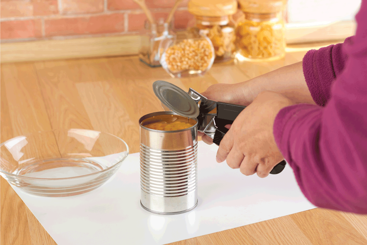 woman-opening-a-can-of-corn-with-can-opener-in-the-kitchen.-How-Long-Should-A-Can-Opener-Last
