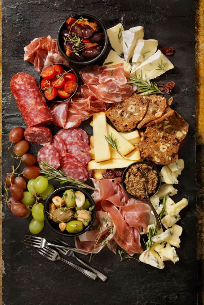 A charcuterie board with different kinds of meat, cheese, and fruit
