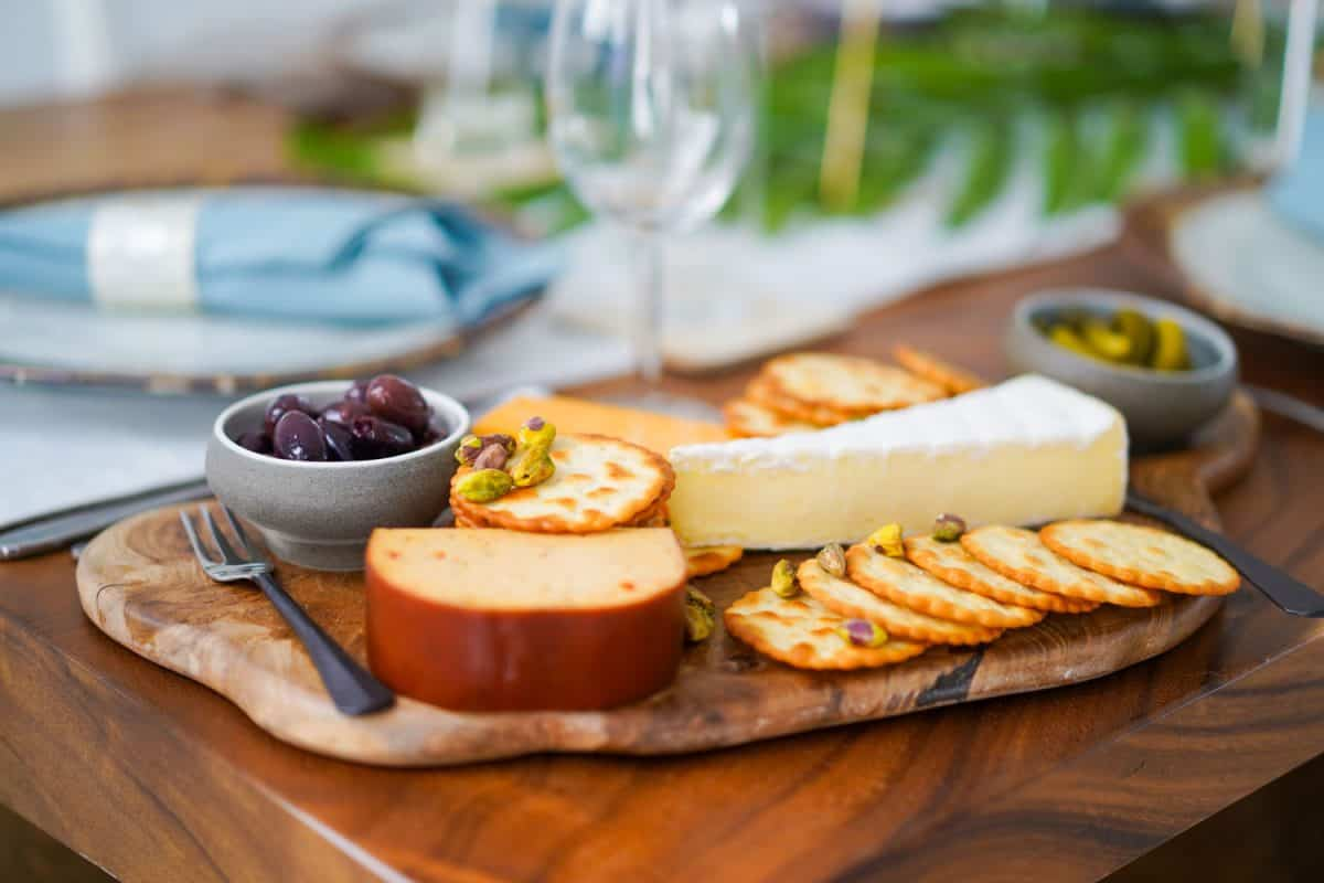 A cheeseboard with a French toast and grapes on the side