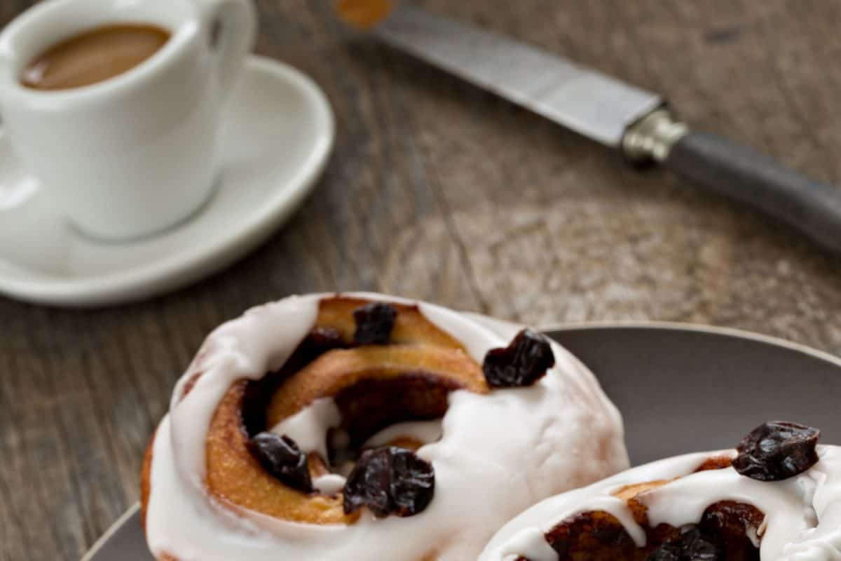 A close up shot of two cinnamon rolls and a small cup of coffee, What Goes With Cinnamon Rolls For Breakfast?