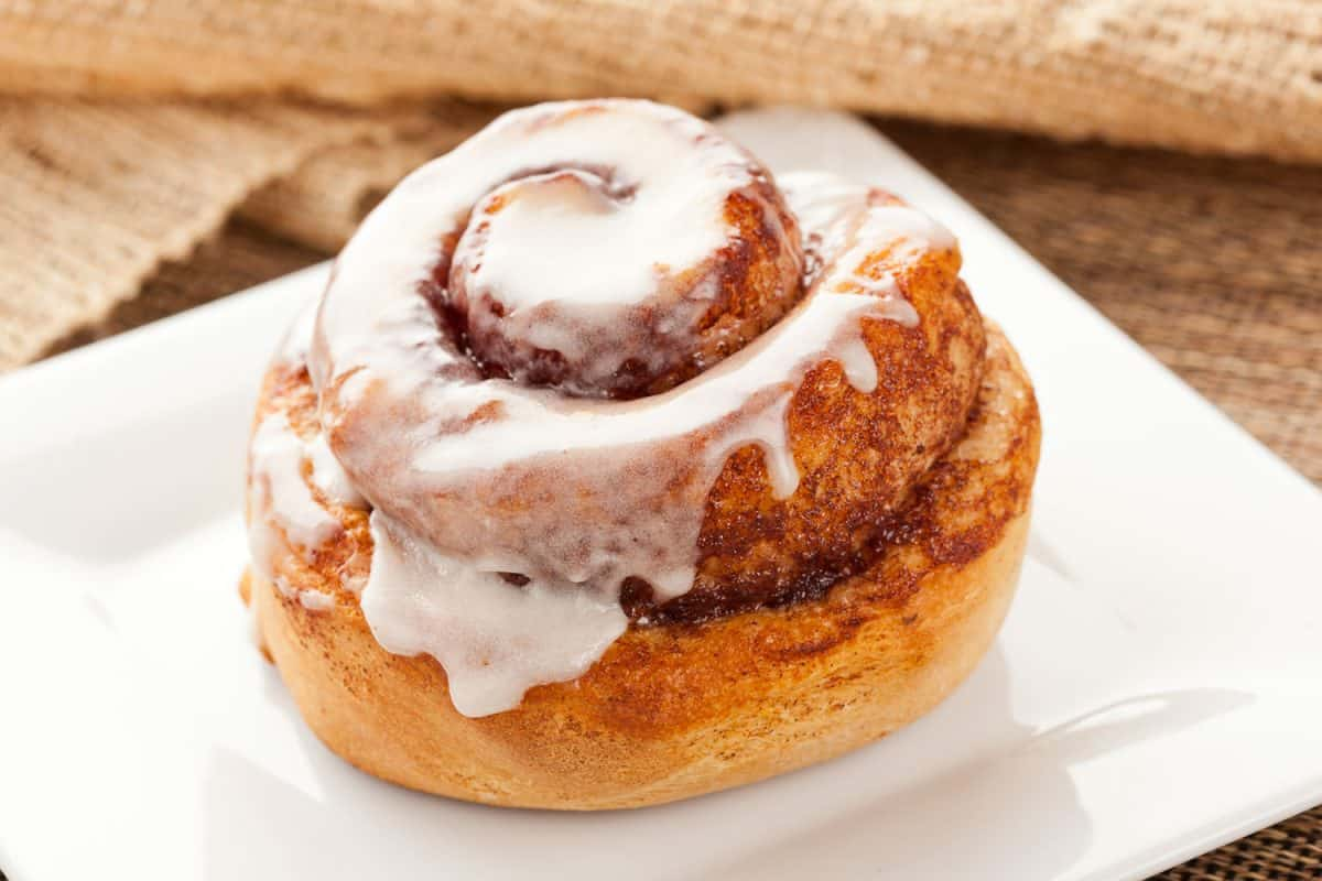 A delicious cinnamon roll on a small white plate