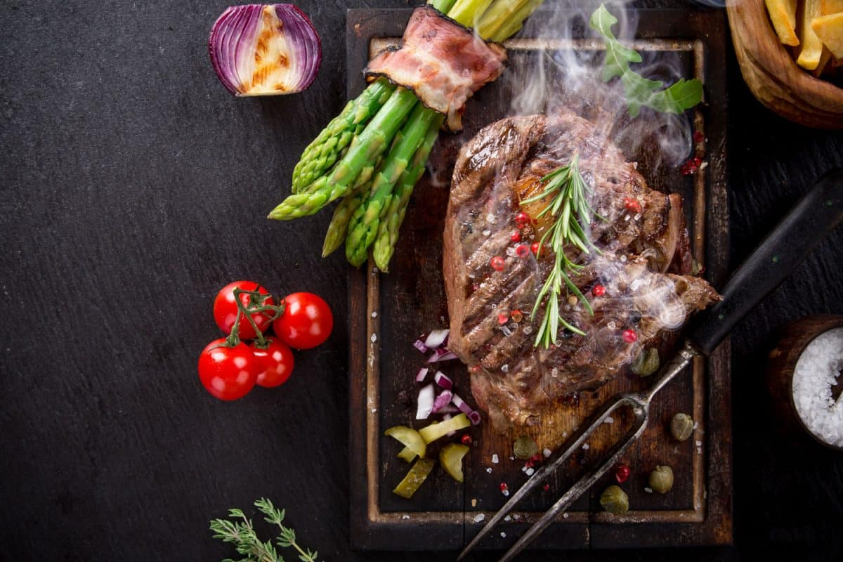 A deliciously roasted beef steak with oregano, asparagus, and small tomatoes on the side
