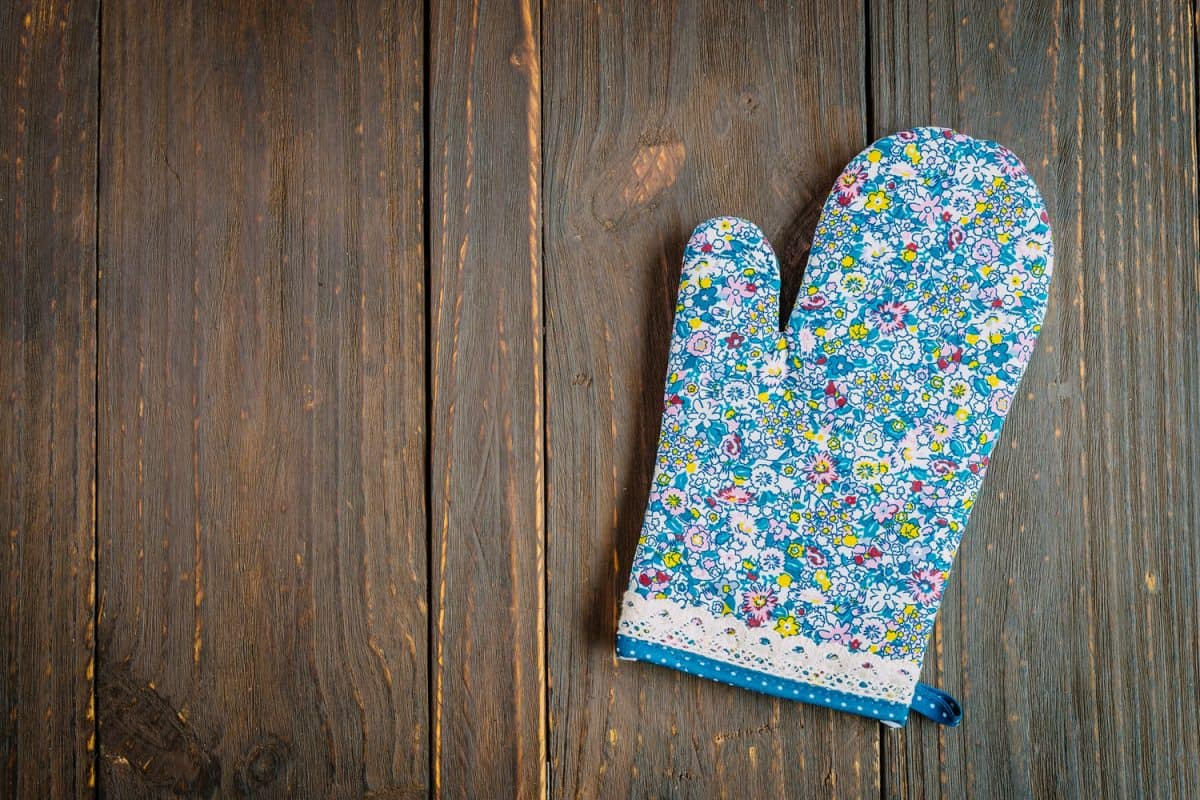 A floral designed oven mitt on top of a table