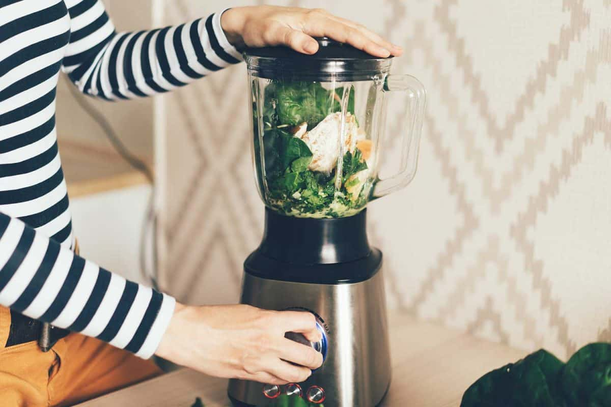 A large blender bowl whips the ingredients for a smoothie