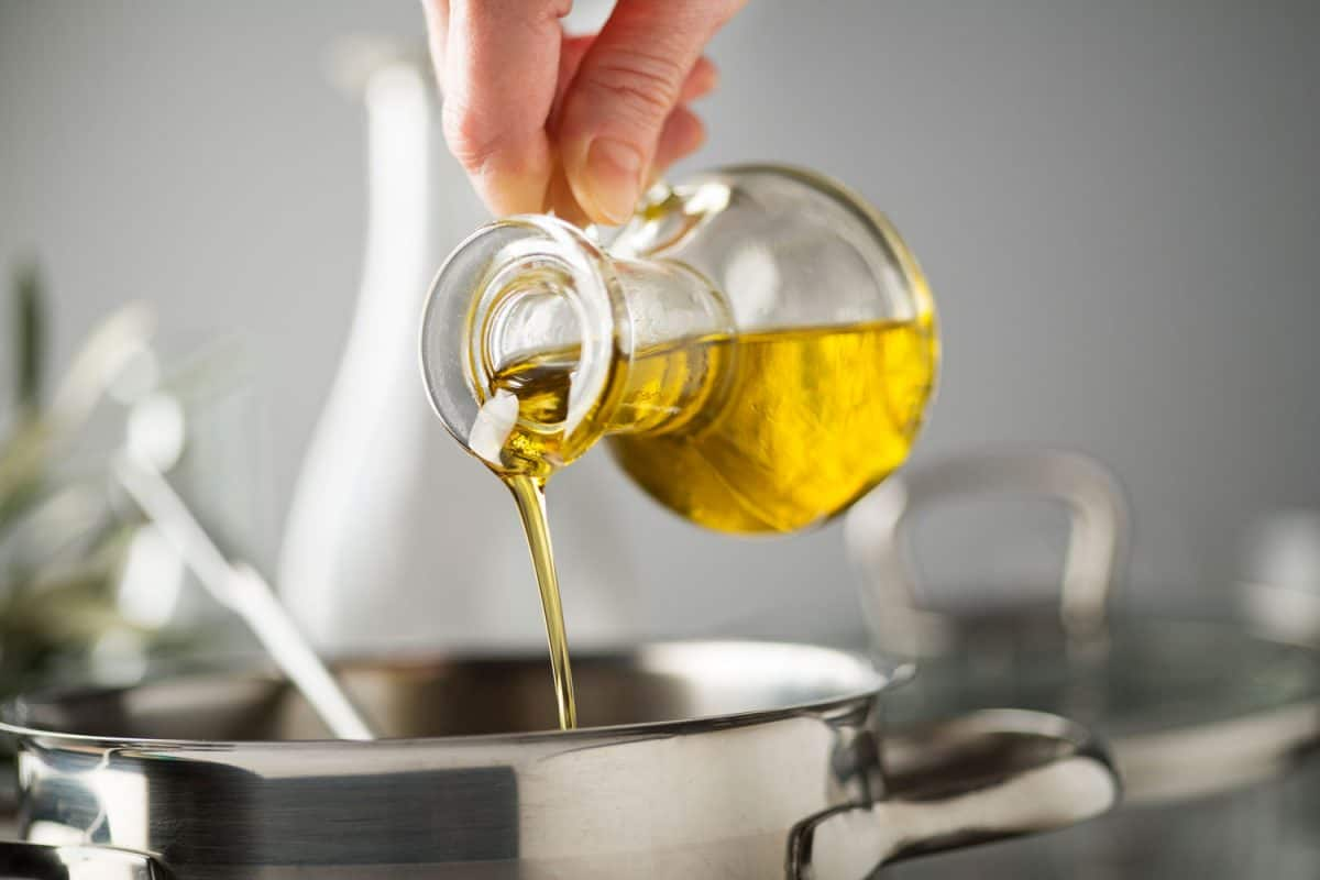A man pouring olive oil on a stainless steel pot