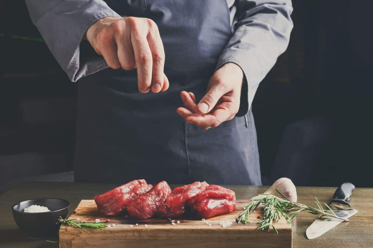 A man sprinkling some salt on four small cut of beef steak