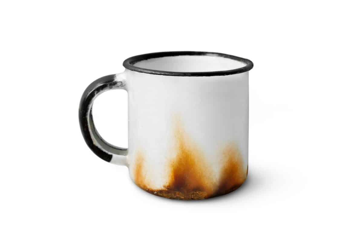 A metal cup with metal rust stain isolated on a white background