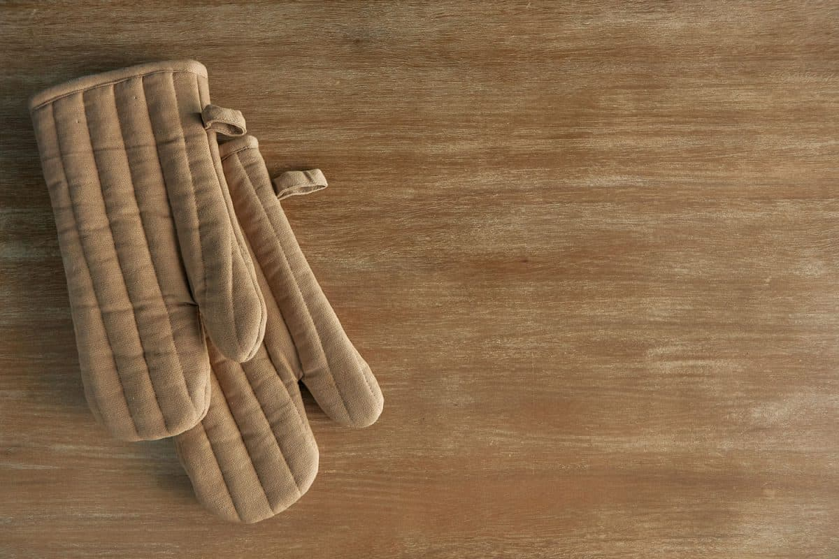 A pair of brown oven mitts on top of a wooden table
