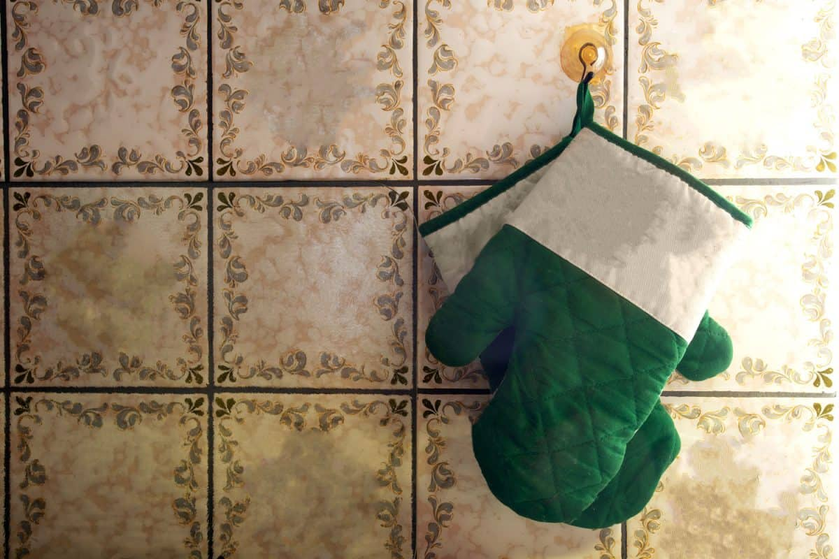 A pair of green oven mitts hanged on a wall