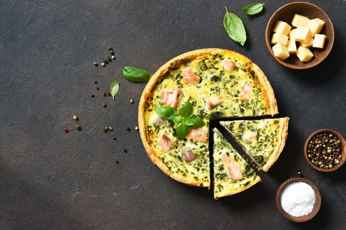 A quiche with salmon spinach and cheese placed on top of a concrete table, Do You Have To Defrost Quiche Before Cooking?