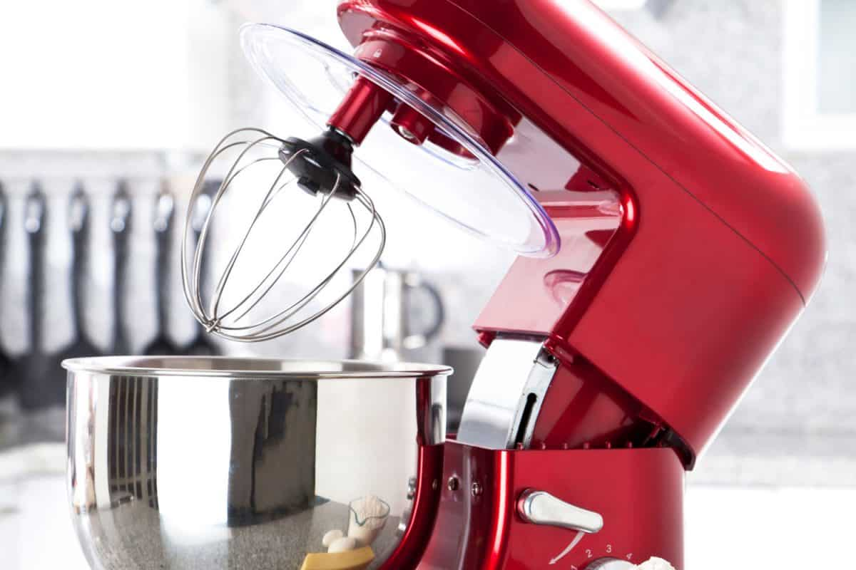 A red electric stand mixer on kitchen counter top with eggs, butter and flour as ingredients for making a pie in the foreground, Can You Fold In With A Kitchenaid Mixer?