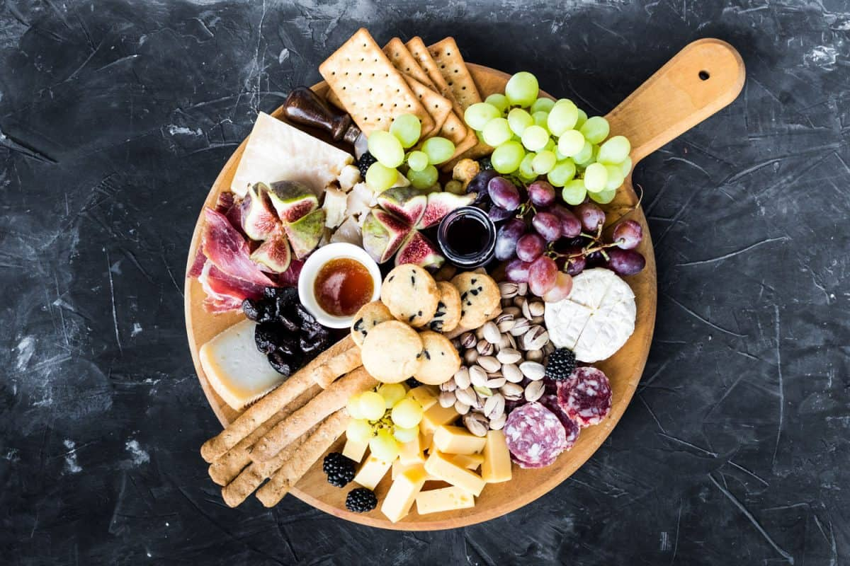 A round cheese board mixed with cheese, fruits, and other beverages on a black countertop