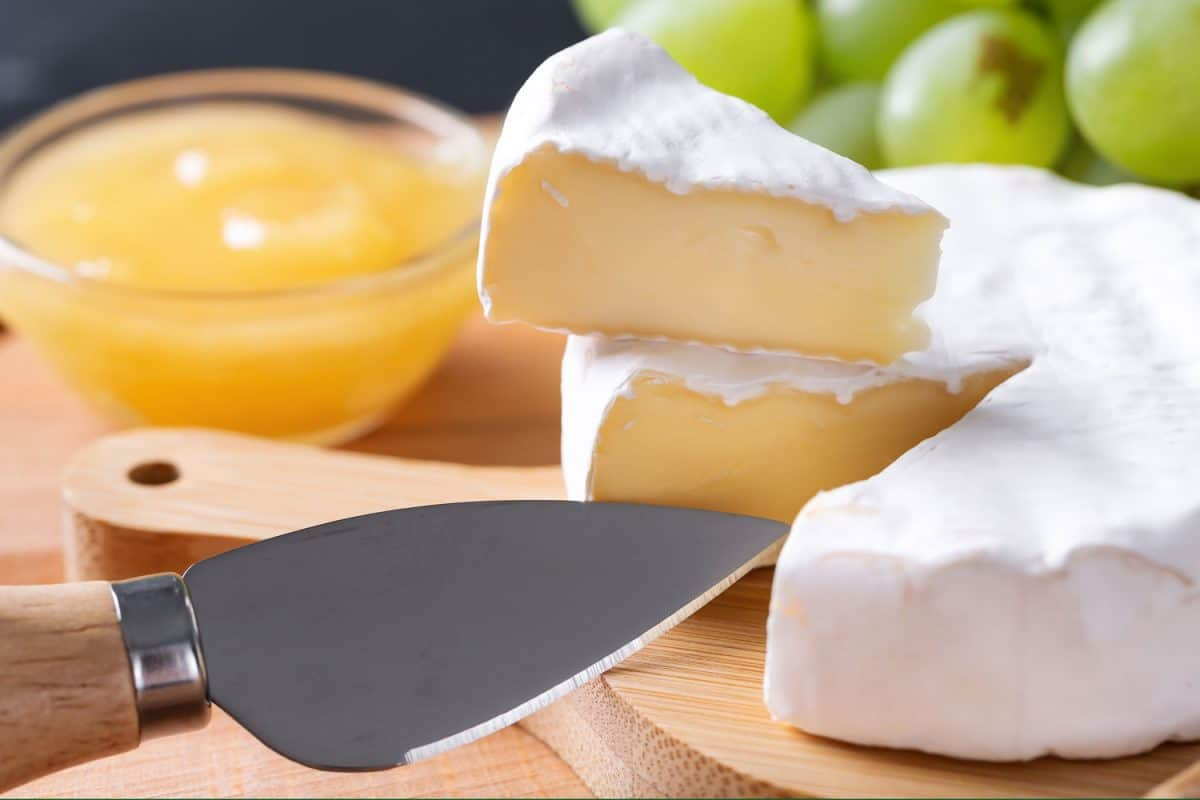 A sliced cheese with knife on a cheeseboard