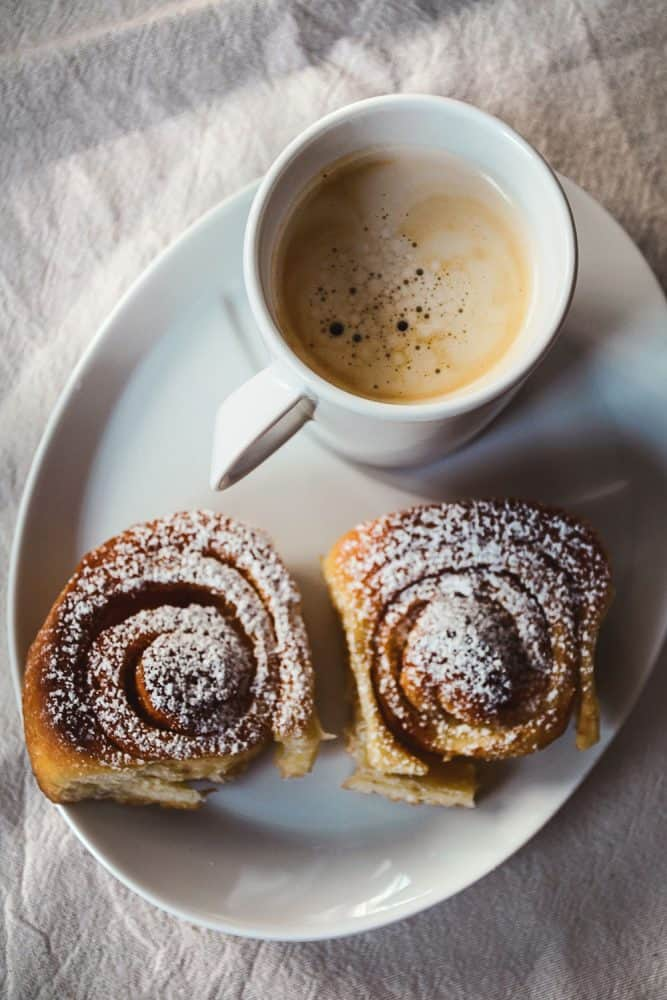 A small morning breakfast with cinnamon rolls and coffee on the side