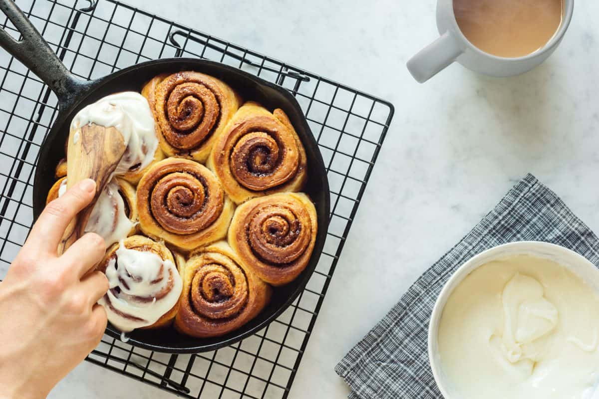 A woman putting icing on the delicious cinnamon rolls
