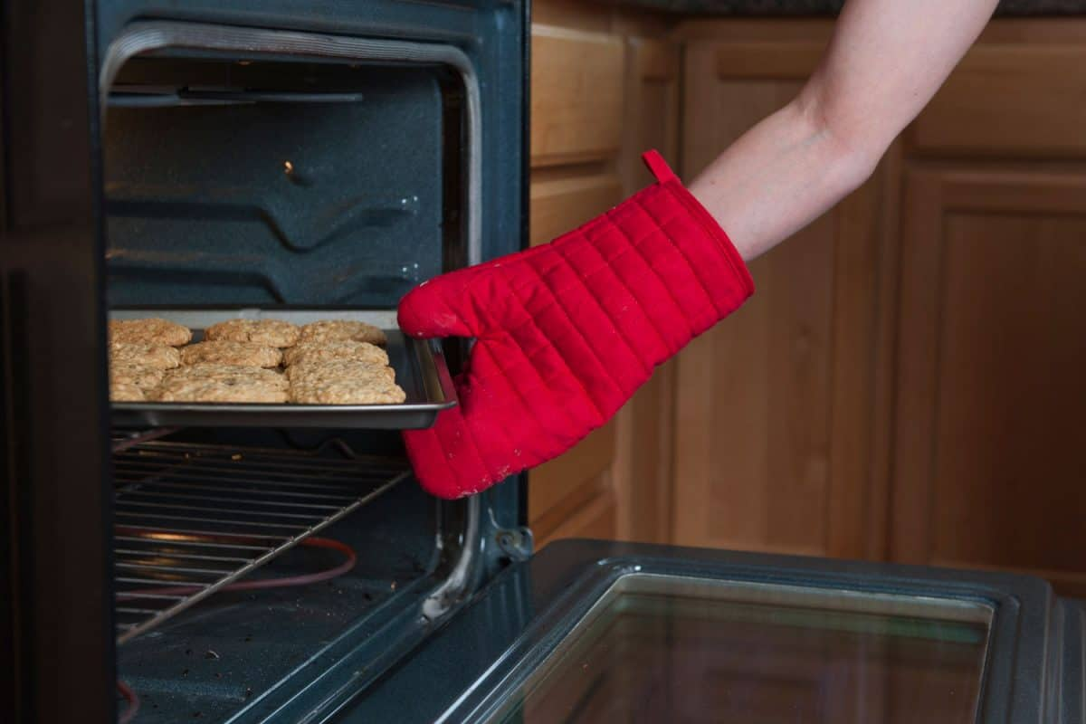 A woman removing freshly baked cookies on the oven