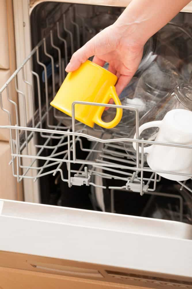 A woman washing a yellow colored Le Creuset mug