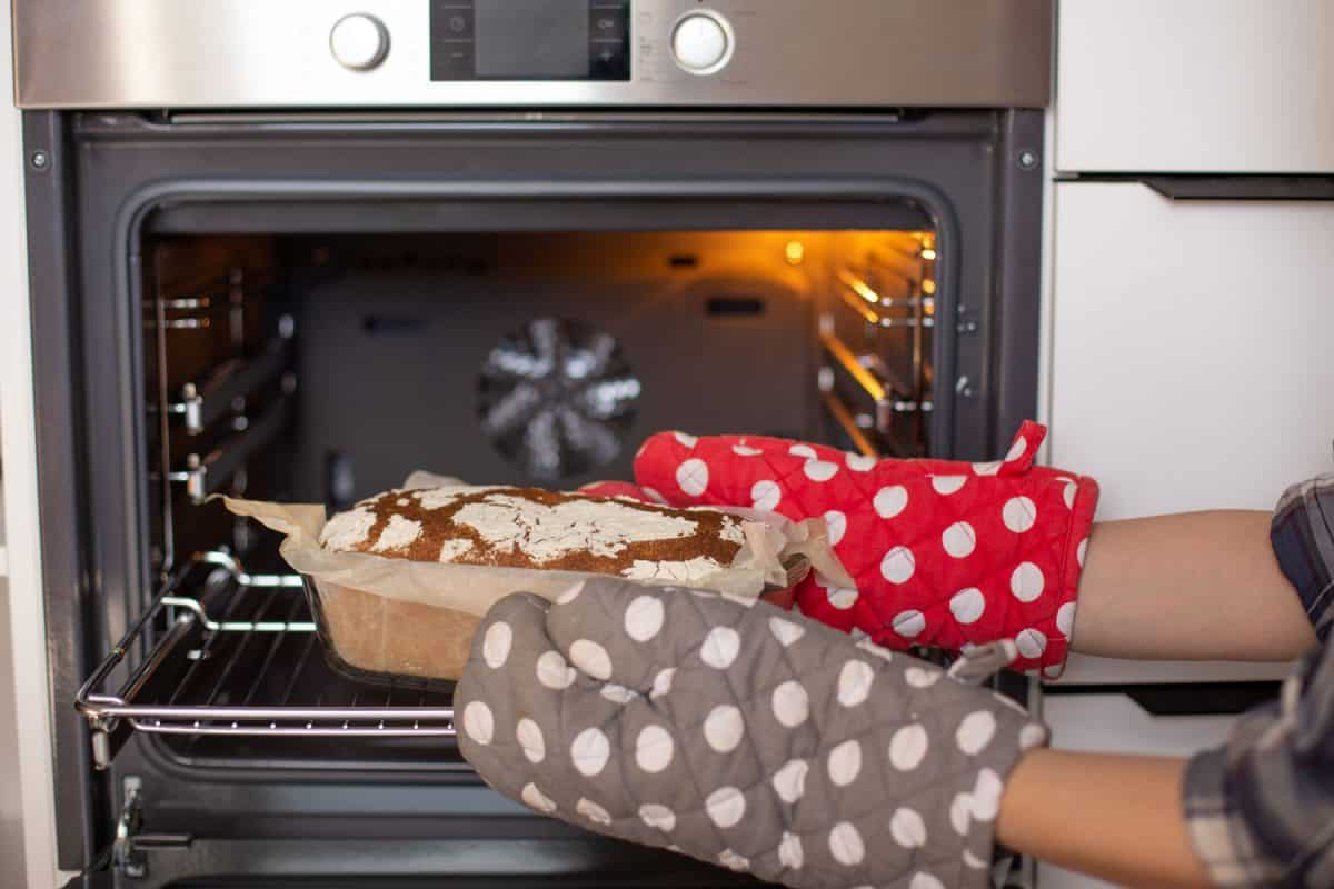 A woman wearing oven mitts removing fresh oven baked bread, Do Oven Mitts Wear Out? [Everything You Need To Know!]