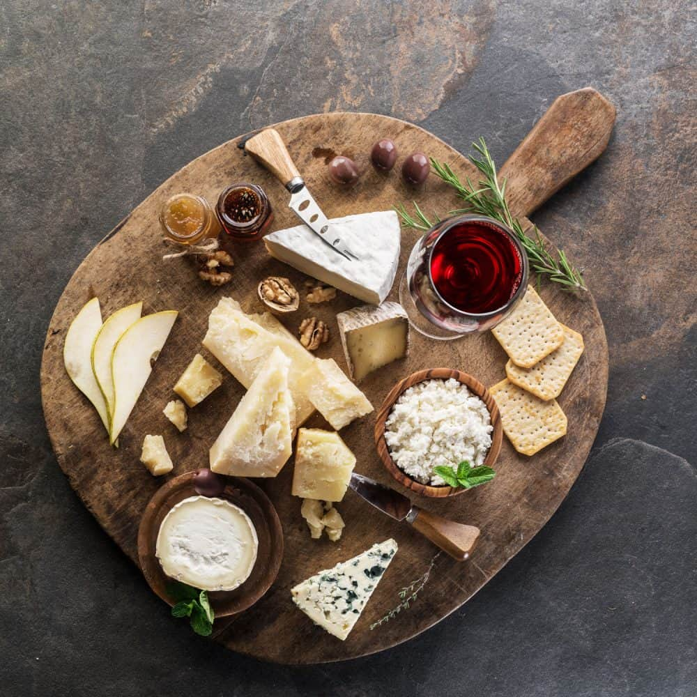 A wooden cheeseboard with different kinds of cheese on top