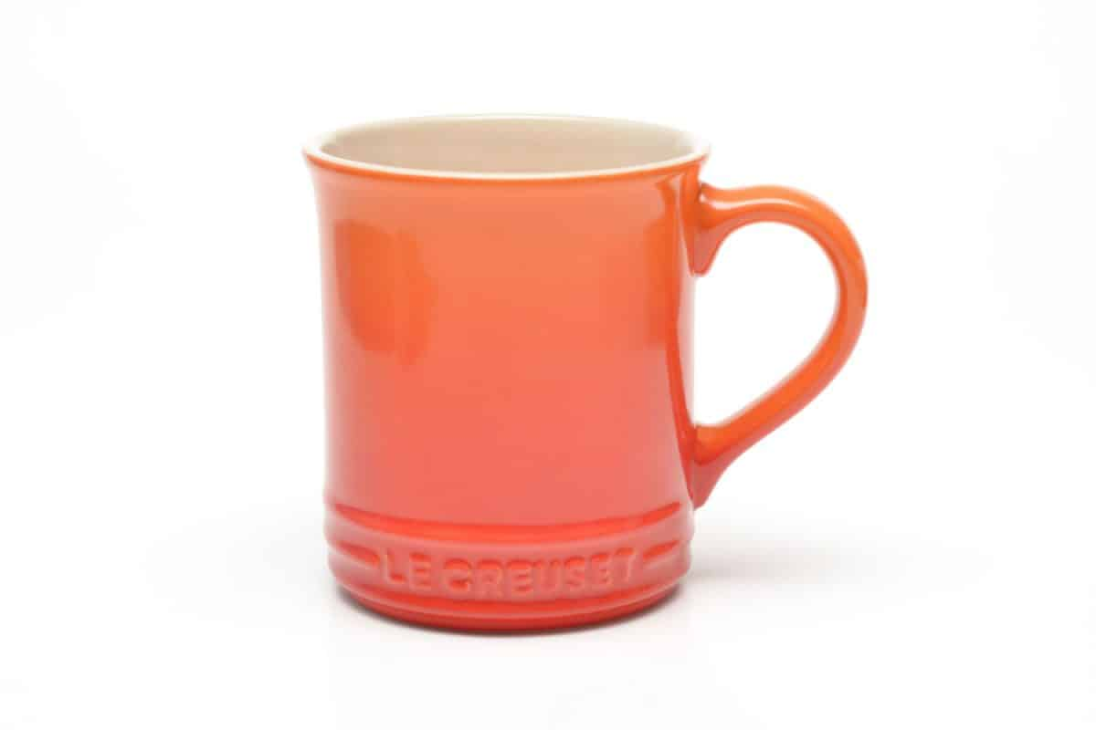 A yellow and red gradient colored Le Creuset mug on a white background