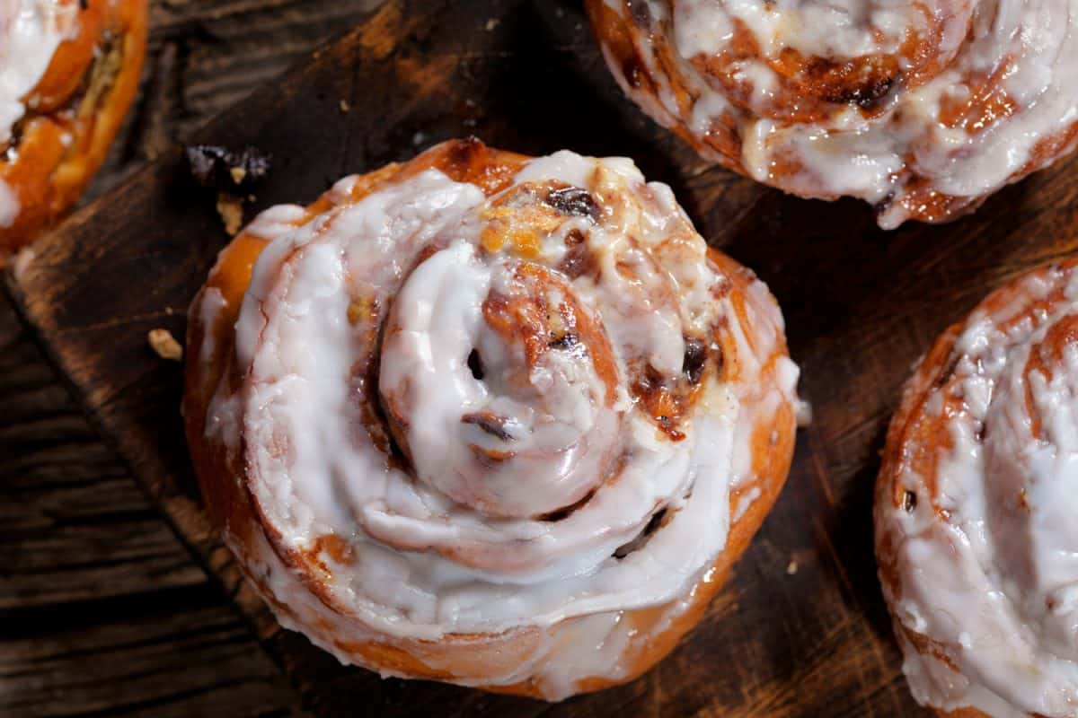 An up close photo of a cinnamon roll with glistening icing