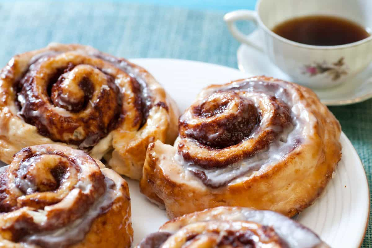 An up close photo of cinnamon rolls with a cup of coffee on the back, How To Keep Cinnamon Rolls Moist