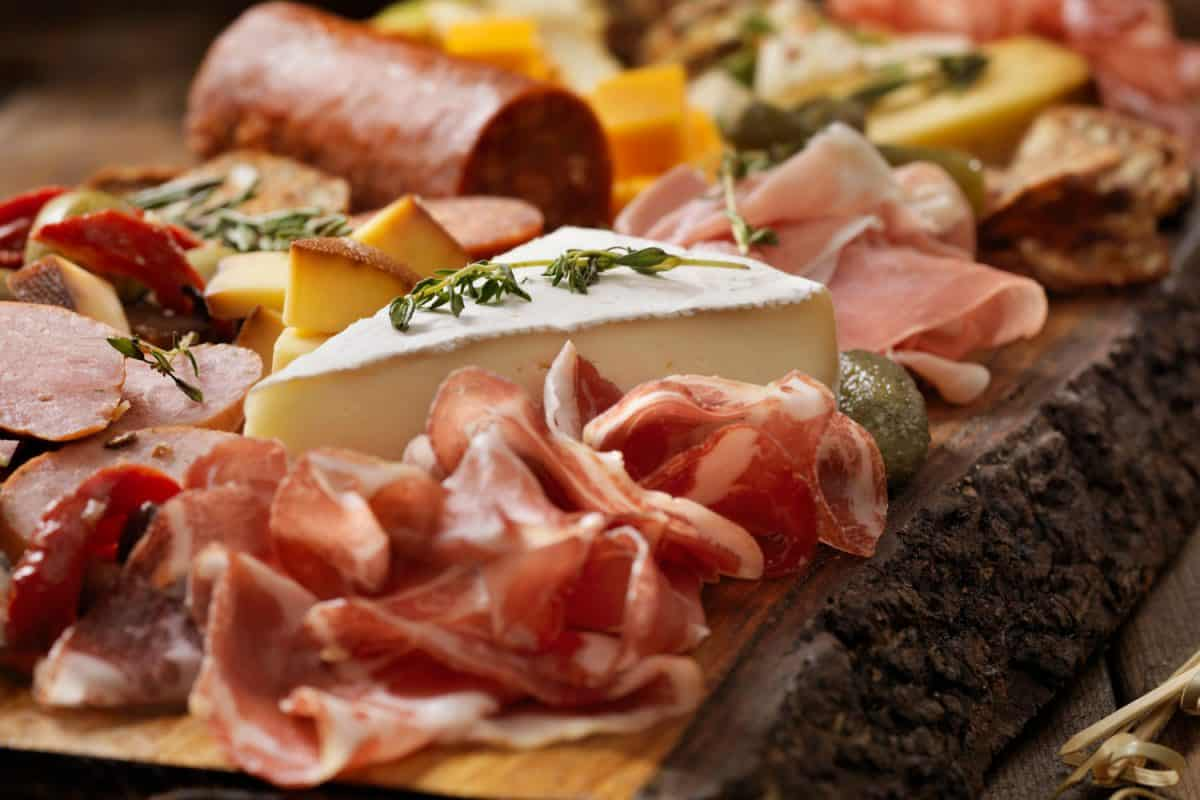 Assorted kinds of meat and cheese on a charcuterie board