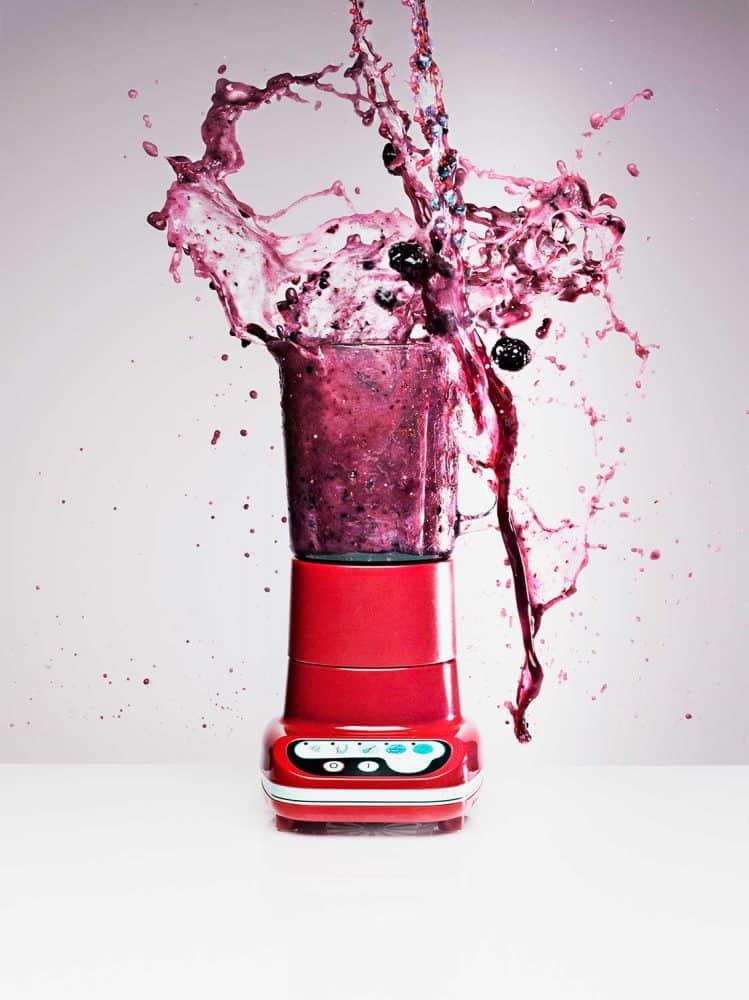 Blueberry juice splashing from blender