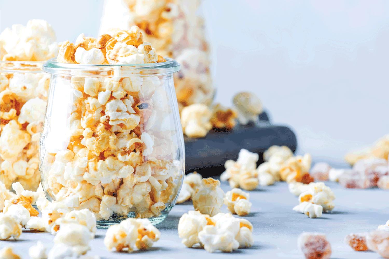 Caramel sweet popcorn in glass jars, gray background