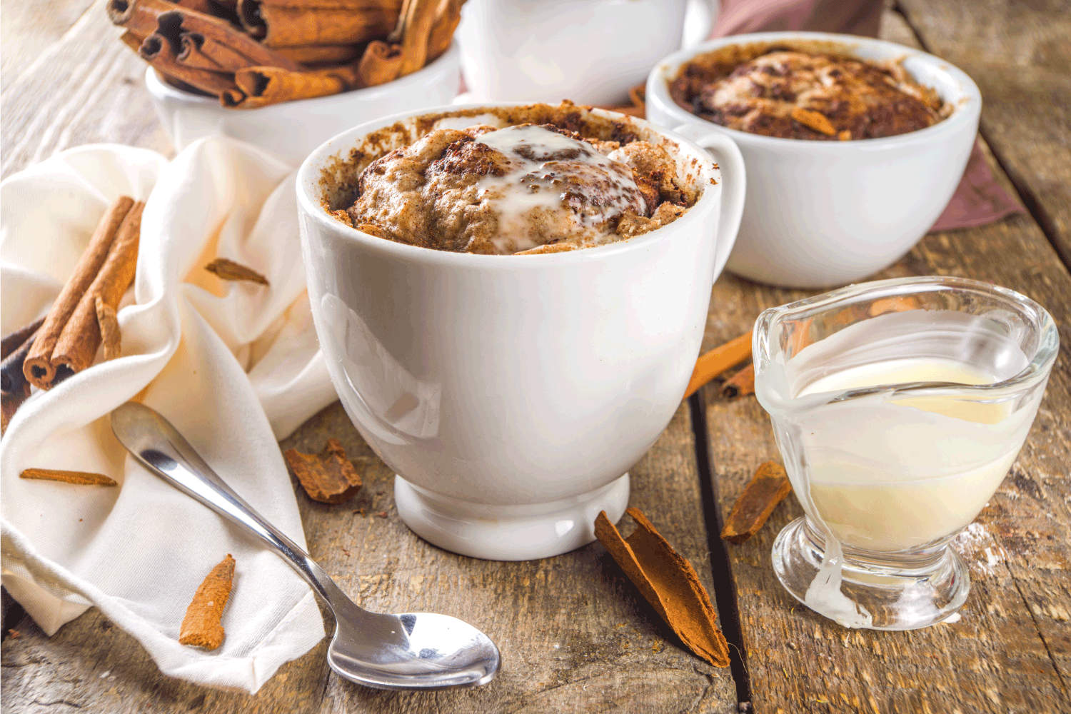 Cinnabon cake in mug. Fast simple microwave dessert idea, background for recipe. Cinnamon roll mugcake, with sugar and cream cheese topping, in different mugs, with cinnamon sticks