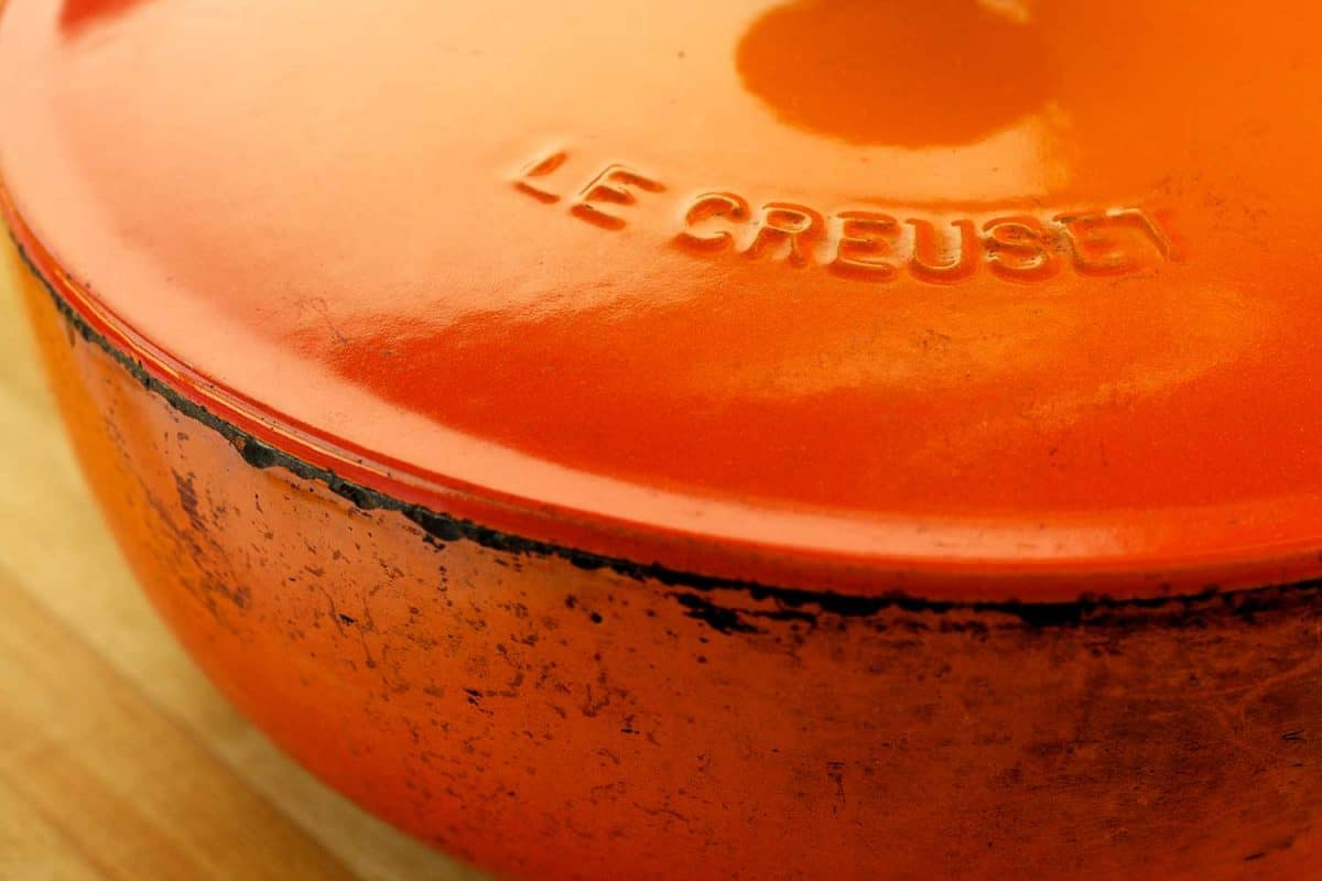 Classic orange Le Creuset enamel coated cast iron cooking pot with distressed marks, Can Le Creuset Ceramic Go On The Stove?