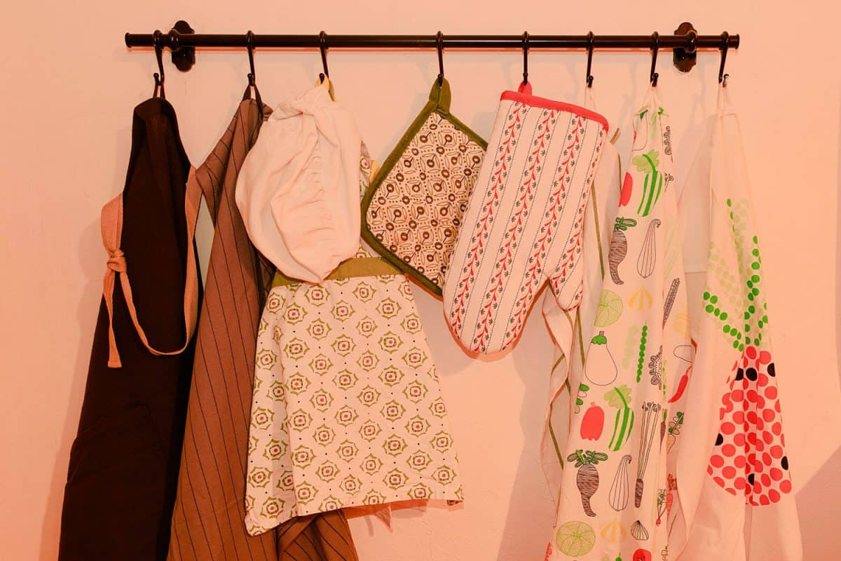 Clean sets of apron and oven mitts hanged on the wall