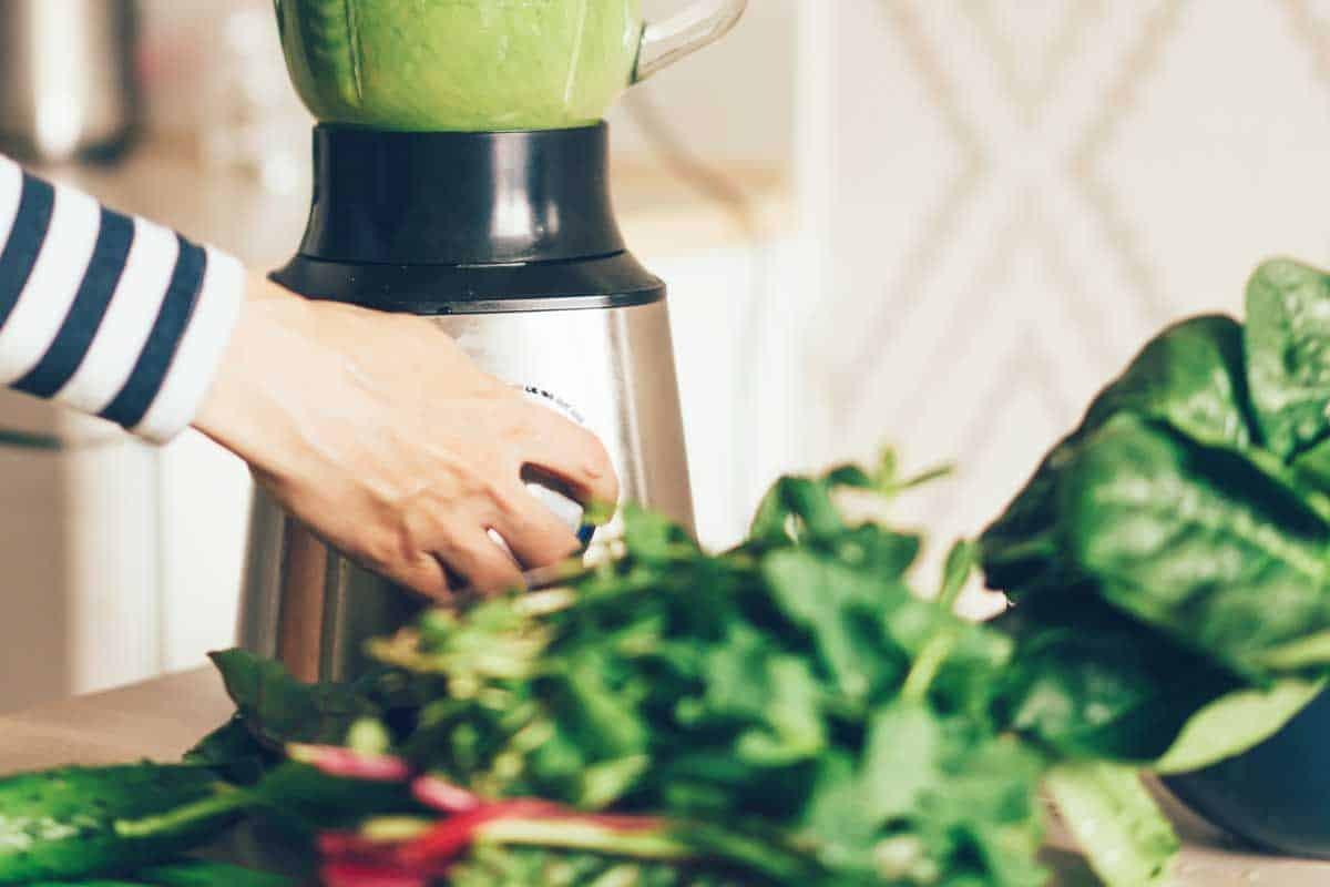 Close up woman hands making green smoothie in blender bowl in interior of kitchen, Can A Blender Chop Vegetables?