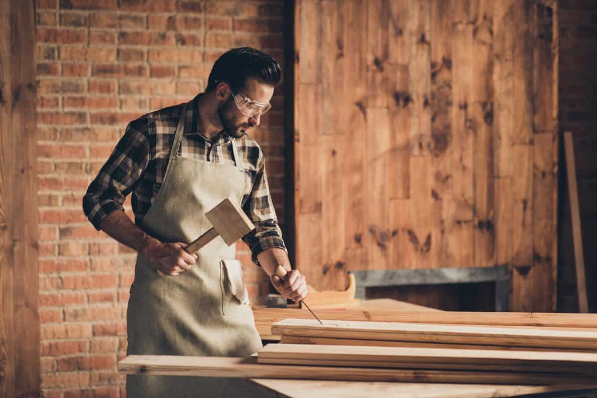 Design people person factory repair shop concept. Side profile close up photo portrait of serious confident brutal stylish concentrated skilled gifted master using metal tool loft furniture interior