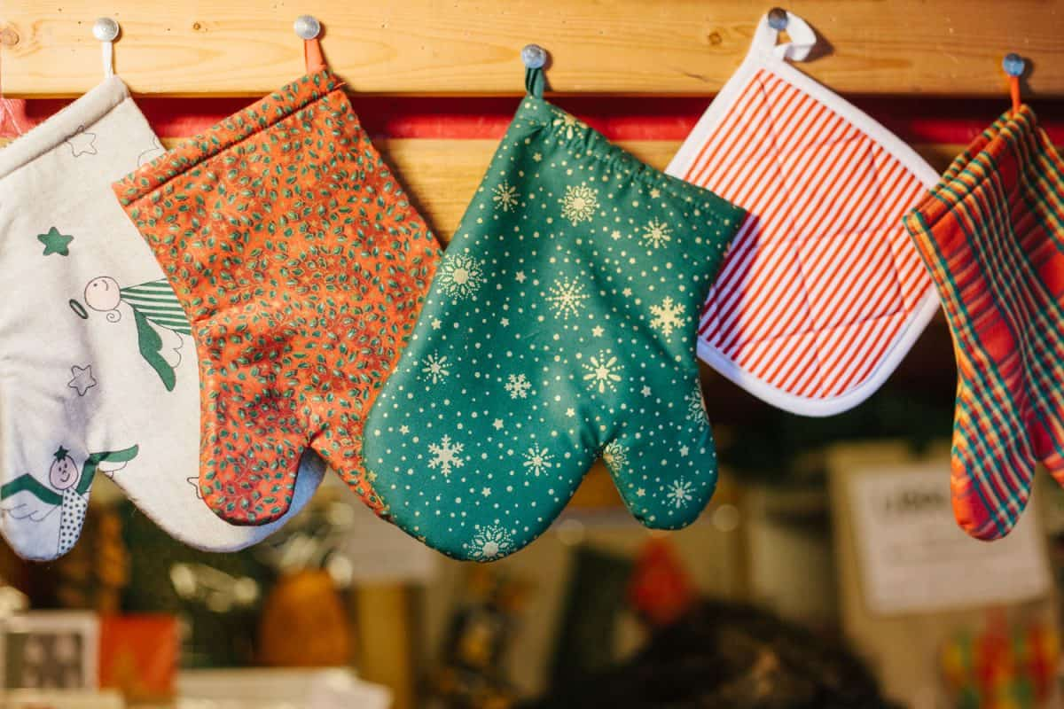 Different colors and designs of oven mitts hanged in the kitchen, Do Oven Mitts Come In Pairs?